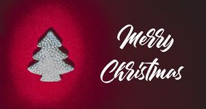 Merry Christmas text in white color on blue background with red christmas tree branches.