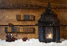 Merry Christmas text on a wooden background with burning lantern. On snowy surface and falling snow stock photos