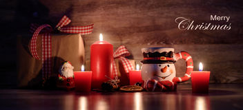 Merry Christmas text on wooden background with lit candles, gifts and snowman mug Royalty Free Stock Images