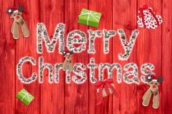 Merry christmas text on wooden red background with reindeer and stock photo