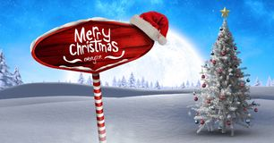 Merry Christmas text on Wooden signpost in Christmas Winter landscape and Santa hat with Christmas t. Digital composite of Merry Christmas text on Wooden Royalty Free Stock Images