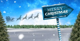 Merry Christmas text on Wooden signpost in Christmas Winter landscape and Santa`s sleigh and reindee. Digital composite of Merry Christmas text on Wooden Stock Images