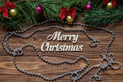 Merry Christmas title on the center of the wooden background with tinsel and a silver chaplet around.  Royalty Free Stock Photo