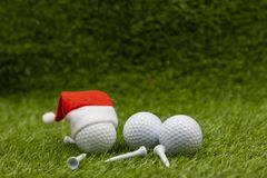 Merry Christmas to golfer with golf ball are on green grass with Christmas ornament