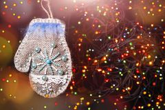Merry Christmas toy mitten with feather. Merry Christmas handmade sackcloth toy mitten with blue feather. blurred background with garland, sparking, glowing and Stock Photography