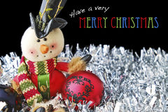 Merry Christmas with Toy Snowman and Baubles on Tinsel Royalty Free Stock Photography