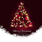 Merry christmas tree bokeh and snow leaf on dark red background. Royalty Free Stock Images