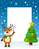 Merry Christmas Tree Frame - Reindeer. Christmas vertical photo frame with a Christmas tree and a happy reindeer smiling and holding a candy cane in a snowy Stock Photos