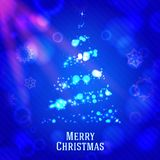 Merry christmas tree made from shining bokeh, on. Blue night background with snowflakes Stock Image