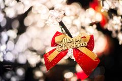 Merry Christmas tree with plenty of lights. And decorations red color bow with golden letters royalty free stock images