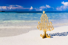 Merry Christmas tree and wishing decoration, in a beach stock image