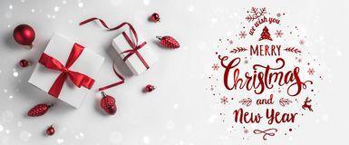 Merry Christmas Typographical on white background with gift boxes and red decoration. Xmas and New Year card, bokeh, light. Flat lay, top view stock images