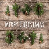 Merry Christmas Typographical on wooden background with fir branches, pine cones and snowflakes on wooden background. Xmas and New. Year theme, snow. Flat lay royalty free stock photos