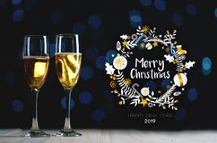 Merry Christmas Typography Art. Two Glasses of Champagne Dark Glow Lights Background royalty free stock images