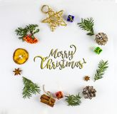 MERRY CHRISTMAS TYPOGRAPHY. FIR BRANCH AND CHRISTMAS DECOR ORNAMENT IN CIRCLE. MERRY CHRISTMAS. DECORATIVE ELEMENTS OVERHEAD PHOTO. BEAUTYFUL ORNAMENT TOOLS stock photo