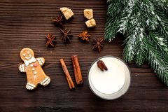 Merry christmas in winter evening with alcohol drink. Eggnog with gingerbread cookie, cinnamon and spruce on wooden desk Stock Photo