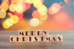 Merry Christmas wish formed on wooden blocks and defocused bokeh Christmas lights background Stock Photo