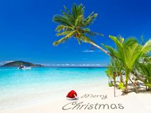 Merry Christmas wishes from the tropical beach. Merry Christmas with santa hat from the tropical beach Royalty Free Stock Image