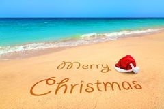 Merry Christmas wishes from the tropical beach. Merry Christmas with santa hat from the tropical beach Stock Photos