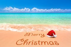 Merry Christmas wishes from the tropical beach. Merry Christmas with santa hat from the tropical beach Stock Photo