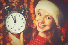 Merry Christmas! woman in Christmas hat with alarm clock. Merry Christmas! Cheerful woman in a Christmas hat with alarm clock Stock Photos