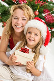 Merry christmas - woman and girl with a present Stock Photos