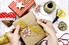 Merry christmas - woman hands wrapping gift box and decorations Royalty Free Stock Photos
