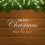 Merry Christmas on wooden background with fir tree branches and. Inscription Merry Christmas and Happy New Year with decorative spruce branches and snow on a Royalty Free Stock Photography