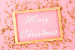 Merry Christmas. A wooden empty frame on a pastel background surrounded by shiny decorative stars and balls. Merry Christmas. A wooden empty frame on a pastel stock image