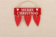 Merry Christmas wooden sign on a pale textured background with space for copy. A cute ,red retro festive Merry Christmas wooden sign with three suspended hanging royalty free stock photography