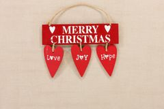 Merry Christmas wooden sign on a pale textured background with space for copy. A cute ,red retro festive Merry Christmas wooden sign with three suspended hanging stock photos