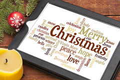 Merry Christmas word cloud. Cloud of words or tags related to Christmas on a  digital tablet with a candle and Xmas decorations Royalty Free Stock Image