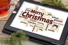 Merry Christmas word cloud. Cloud of words or tags related to Christmas on a digital tablet with a cup of tea royalty free stock images