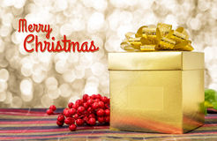 Merry Christmas word with Gold present box and ribbon on table w Royalty Free Stock Images