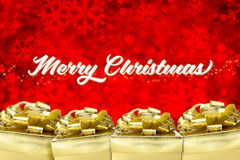 Merry christmas word with Golden present box with big bow at red Royalty Free Stock Image