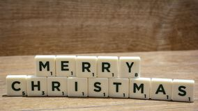 MERRY CHRISTMAS word written in wooden blocks on brown background. royalty free stock photos