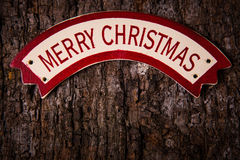 Merry Christmas words on banner over old wood surface Stock Photos
