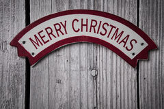 Merry Christmas words on banner over old wood surface Stock Images