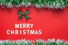 MERRY CHRISTMAS words and ribbon bow with glitter frame on red background Royalty Free Stock Photos