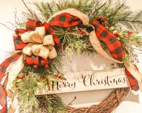 Merry Christmas Wreath With Red Plaid Bows. A Merry Christmas grapevine wreath with evergreen branches, pine cones, red and black plaid ribbon and tan bows with royalty free stock photography