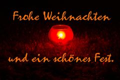 Merry Christmas, writhing in German. Candle light in snow. Royalty Free Stock Images