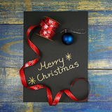 Merry Christmas written on black card with christmas ribbon and bauble Royalty Free Stock Image