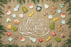 Merry Christmas! written among gingerbread cookies surrounded with fir branches. Royalty Free Stock Photography