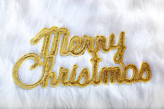 Merry christmas written in gold on white fur Royalty Free Stock Photos