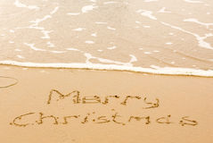 Merry Christmas written in sand on beach Royalty Free Stock Image