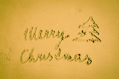 Merry Christmas written into sand Royalty Free Stock Photos