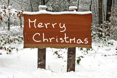 Merry Christmas written on a snowy wooden sign Royalty Free Stock Photos