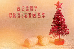 Merry Christmas written by sparkly red brush. Red artificial Christmas tree with champagne cork on bright background Royalty Free Stock Photo