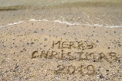 Merry Christmas 2019 written on tropical beach sand, copy space. Holiday concept, top view royalty free stock photography