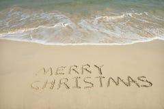 Merry Christmas written on tropical beach white sand Stock Image